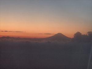 飛行機から見えた夕日と富士山のシルエット